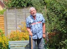 走与藤茎的易碎的老人 免版税库存图片