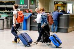 走与行李的人们在机场 免版税库存图片