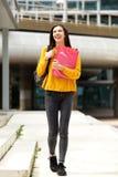 走与袋子和书的少妇学生 免版税图库摄影
