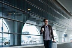 走与袋子和咖啡的一个愉快的男性旅客的充分的身体画象 库存照片