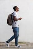 走与袋子和手机的微笑的男性大学生 免版税库存图片