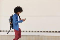 走与袋子和手机的男学生 免版税库存照片