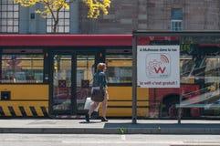 走与袋子的妇女在火车站前面的汽车站 免版税库存图片