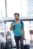 走与袋子的微笑的人在火车站 免版税库存照片