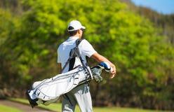 走与袋子的高尔夫球运动员 库存照片