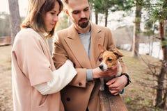 走与起重器罗素狗狗一起的年轻愉快的浪漫夫妇在秋天 库存照片