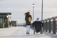 走与轮椅的残疾人的少妇背面图在码头 图库摄影