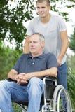走与轮椅的残疾父亲的儿子在公园 免版税库存照片