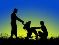 走与婴儿推车的一个愉快的家庭的剪影在日落 图库摄影