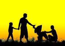 走与婴儿推车的一个愉快的家庭的剪影在日落 免版税库存图片