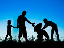走与婴儿推车的一个愉快的家庭的剪影 免版税库存图片