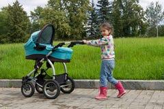 走与婴儿推车的小女孩 库存图片