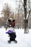 走与婴儿推车的婴孩的年轻母亲在冬天公园 库存图片