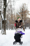 走与婴儿推车的婴孩的年轻母亲在冬天公园 库存照片