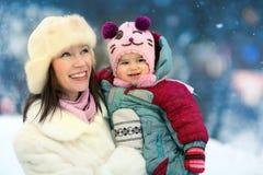 走与婴孩的母亲在冬天公园 免版税库存照片