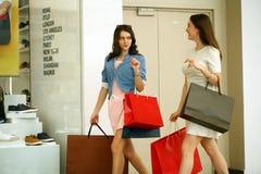 走与购物的两个少妇在商店 免版税库存图片