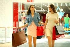 走与购物的两个少妇在商店 库存照片
