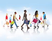 走与购物袋的小组不同的人民 免版税库存照片