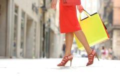 走与购物袋的顾客腿 免版税库存照片