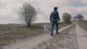 走与他的沿土路的狗的年轻人 股票视频