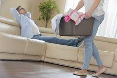 走与洗衣篮的妇女的低部分,当放松在沙发的人在背景中时 免版税库存照片
