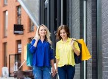 走两名美丽的妇女握有购物袋的手 图库摄影