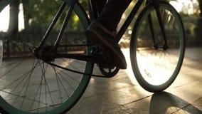 走乘在被铺的路关闭的自行车的男性匿名的腿侧视图活跃生活方式 人男孩连同黑色 股票录像