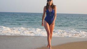 走从海洋的年轻女人到与波浪的海滩在背景 泳装的美女跨步海上的 影视素材