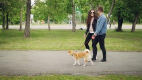 走他的宠物和聊天对他的女朋友去的手的可爱的年轻人狗所有者慢动作侧视图  股票视频