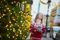 走以热的饮料的女孩去在巴黎街道上为圣诞节装饰了 库存照片