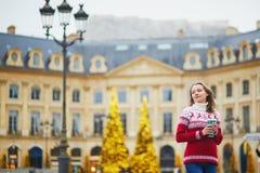 走以热的饮料的女孩去在巴黎街道上为圣诞节装饰了 免版税库存图片