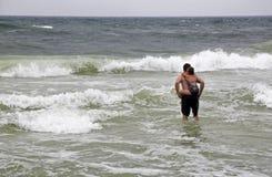 走入海浪的父亲和女儿 免版税库存图片