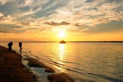 走入水的人们在海滩在日落期间在夏天 免版税图库摄影