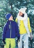 走冬日、愉快的母亲和儿童儿子的家庭在明亮的运动服一起穿戴了在圣诞树 图库摄影