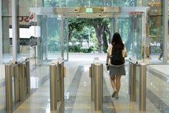 走出去从安全的妇女人在有钥匙卡片存取控制聪明的办公楼的一个入口门 库存照片