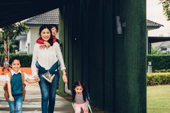 走出去从家庭举行的手她的孩子的亚裔愉快的母亲 免版税库存图片