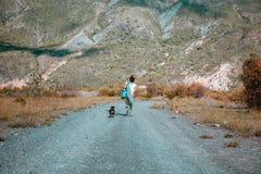 走到与狗的山的妇女 库存照片