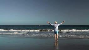 走到在海洋海滩的水的愉快的年轻人在日落 无忧无虑的现代生活的概念 慢的行动 股票视频