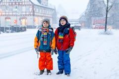 走到学校的基本的类的两个小孩男孩在降雪期间 获得乐趣和使用与的愉快的孩子 库存照片