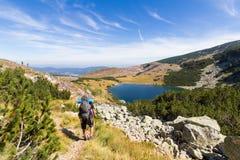走到山湖的背包徒步旅行者 免版税库存图片