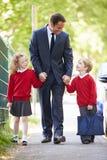 走到有孩子的学校的父亲在途中工作 免版税库存图片