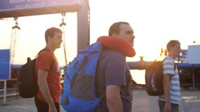 走到有背包徒步旅行者的轮渡的旅客人在美好的日落和透镜火光作用期间 库存图片