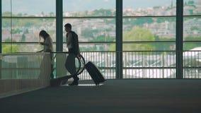走到自动扶梯的商务旅行、男人和妇女在机场,运载的行李 股票视频