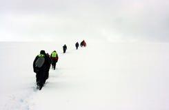 走到雪展望期的人们 库存照片