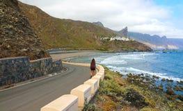 走到Anaga山的Almaciga小的村庄的女性徒步旅行者背包徒步旅行者在大西洋,特内里费岛 库存图片