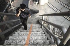 走台阶的亚裔人在城市谈话在手机。 免版税图库摄影