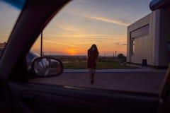 走向有日落的一辆汽车的妇女在背景 库存照片