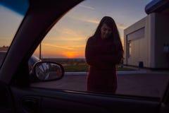 走向有日落的一辆汽车的妇女在背景 免版税图库摄影