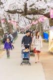 走和享用樱花的人们在日本 免版税库存照片