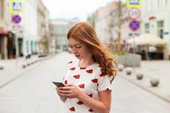 走和使用一个巧妙的电话的时尚愉快的女孩的正面图 免版税图库摄影
